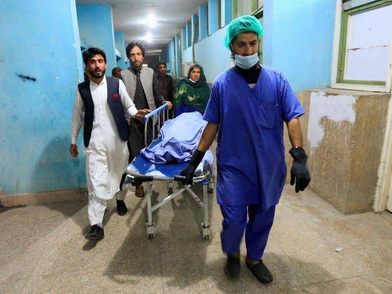 Hospital staff escort the body of one of three female media workers shot and killed in Afghanistan.
